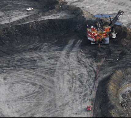 Zoomed image showing excavator, and dump  truck hauling away spoil and oil/tar sands. Image: Edward Burtynsky
