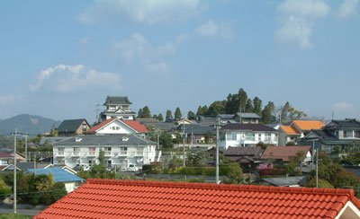 A miniature castle in Kokubu, seen over suburban rooves. Image credit: the auroran sunset