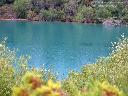 Blue lake with greens and yellows around. Image credit: the auroran sunset