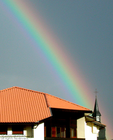 It's a sign: rainbow going into a church. Image credit: abelard